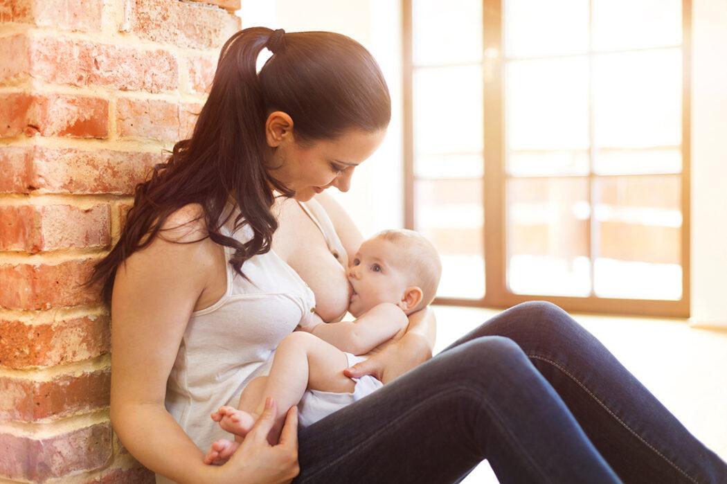 junge Frau stillt Baby