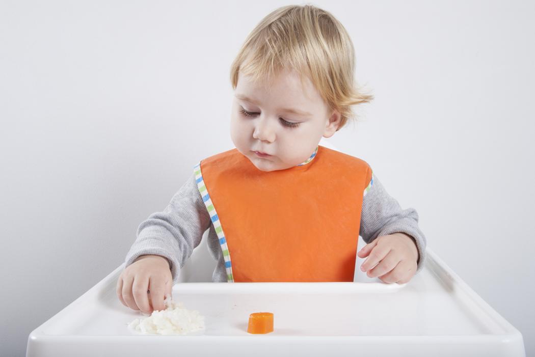 Baby isst Reis und Karotten