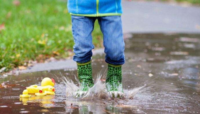 Kind springt bei Regen in die Pfütze reien bei Regen