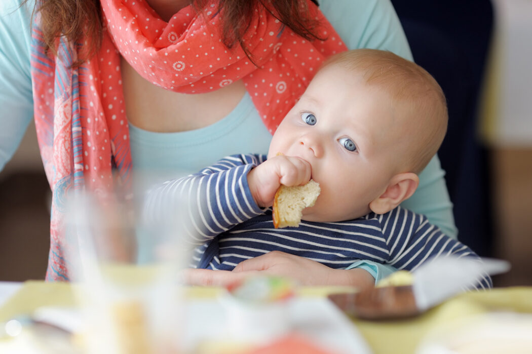 Baby isst ein Stück Brot
