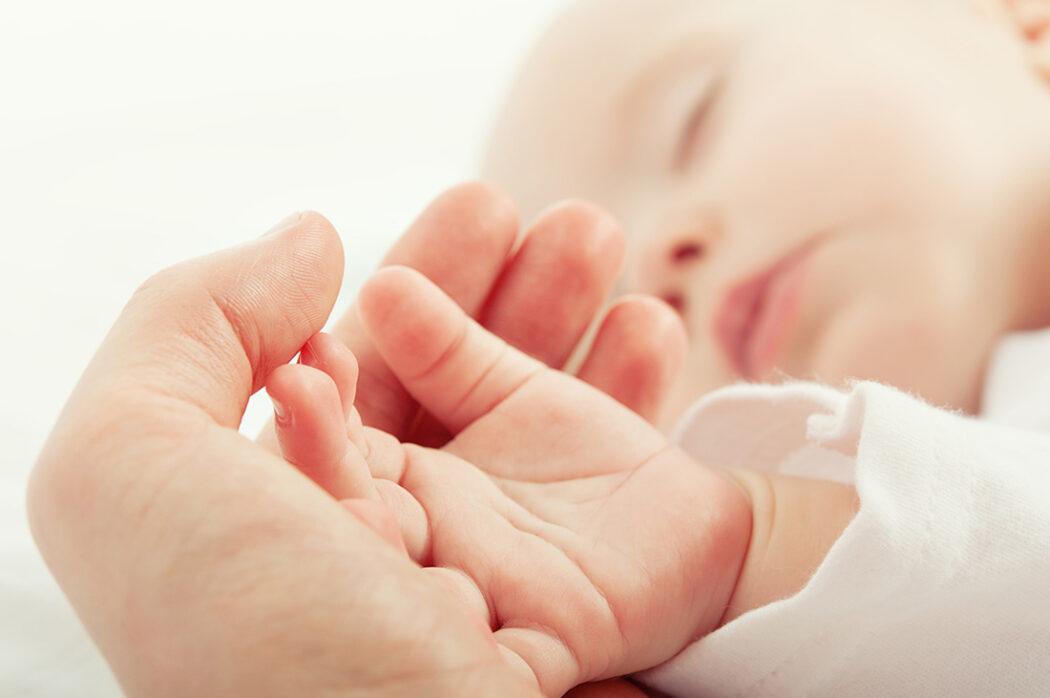schlafendes Baby hand in hand mit Mutter