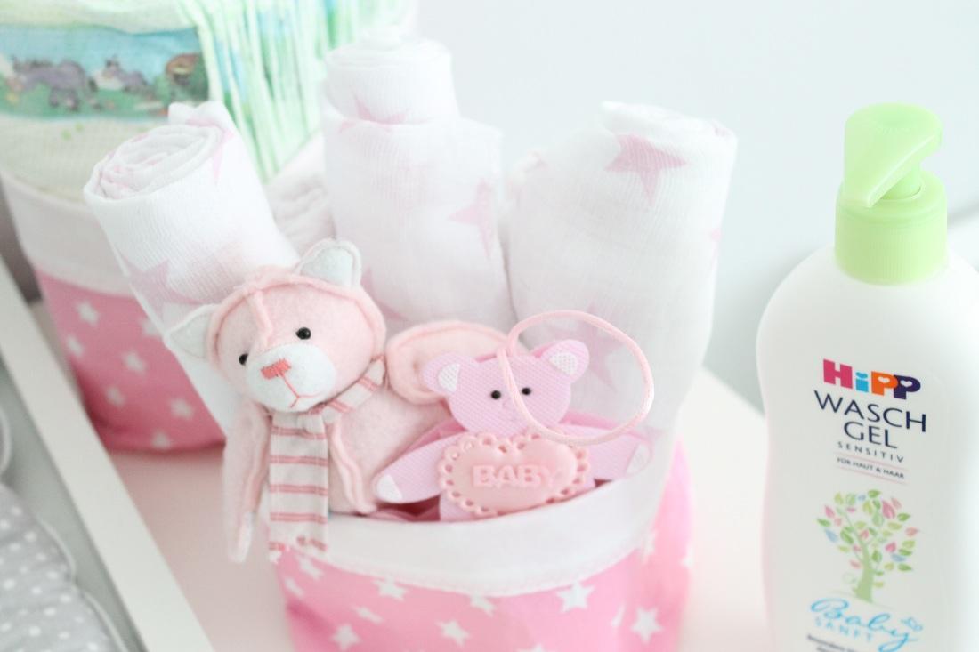 Mullwindeln und Spielzeug in Utensilos griffbereit am Wickeltisch