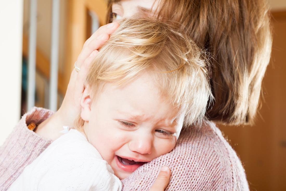 Mutter hält weinendes Kleinkind im Arm