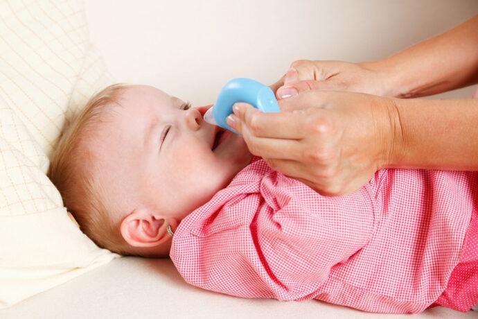 Babys Nase wird gesäubert mit Nasensauger