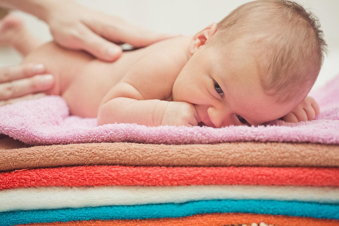 Neugeborenes Baby wird eingecremt