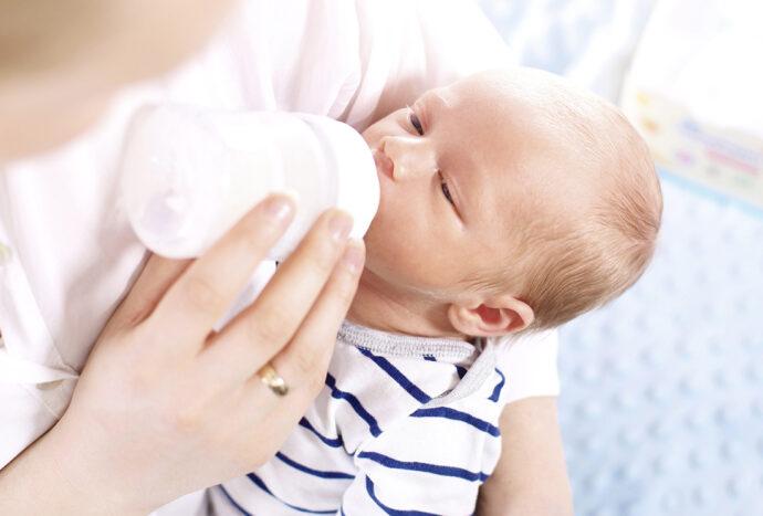 Neugeborenes Baby trinkt aus Flasche