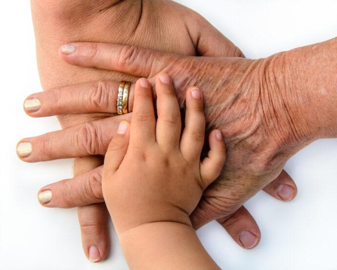 Hände dreier Generationen übereinander