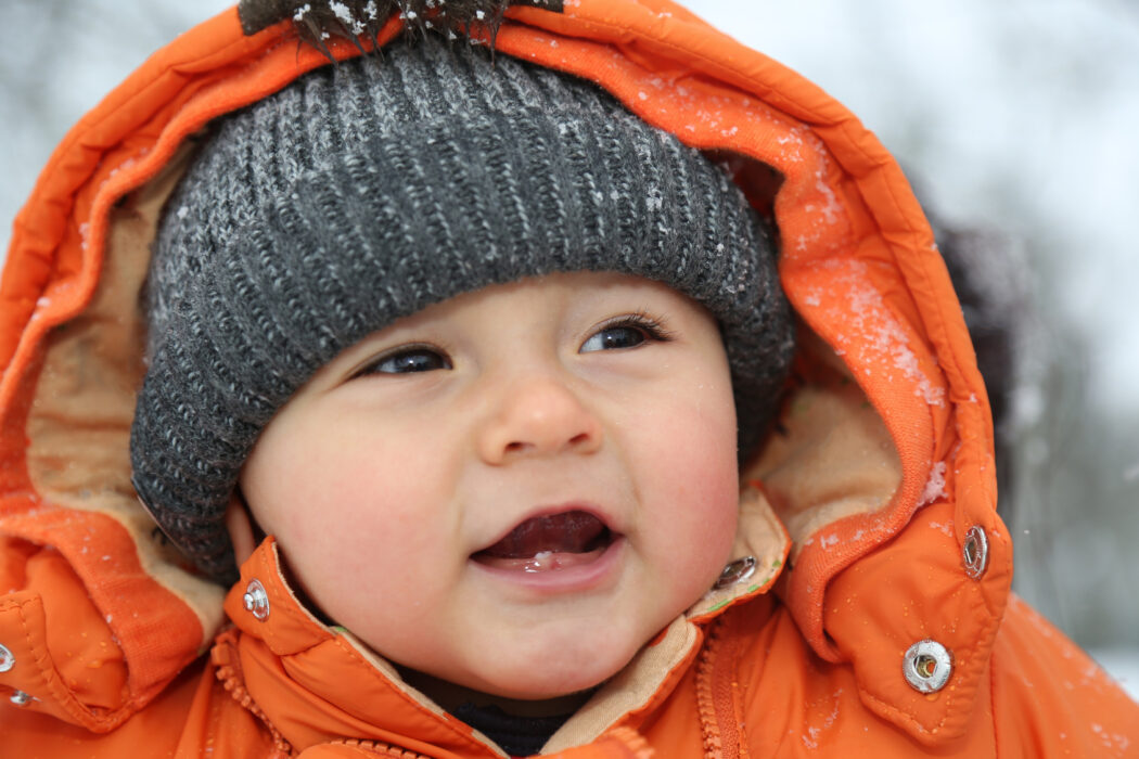 Portrait lachendes Baby im Schnee im Winter
