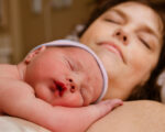 Bonding: Neugeborenes Baby kuschelt mit seiner Mama