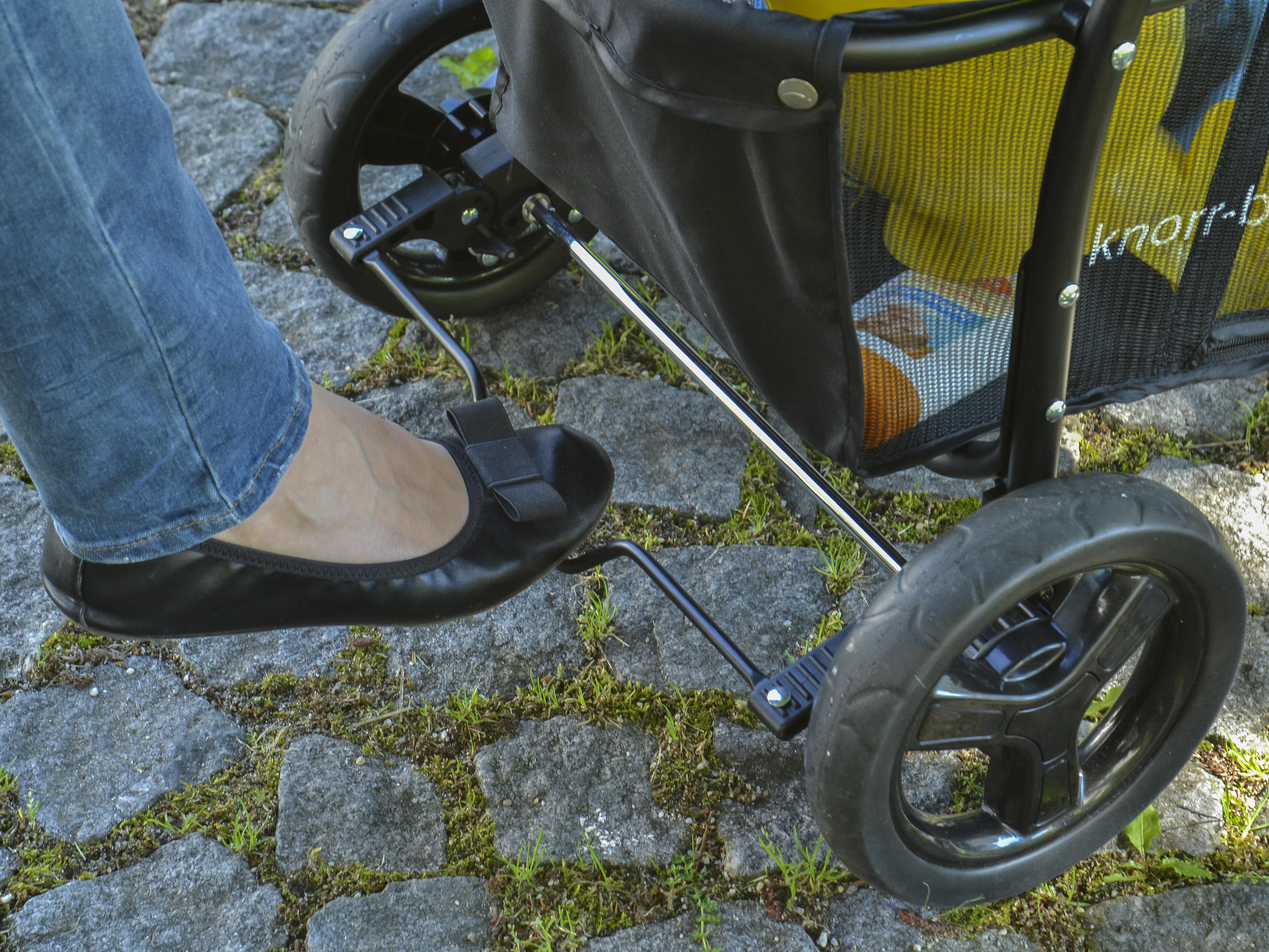 Mit dem Fuß bedienst Du die Feststellbremse, leider ist diese nicht besonders schuhschonend.