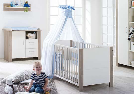 Kleiner Junge vor Kinderbett