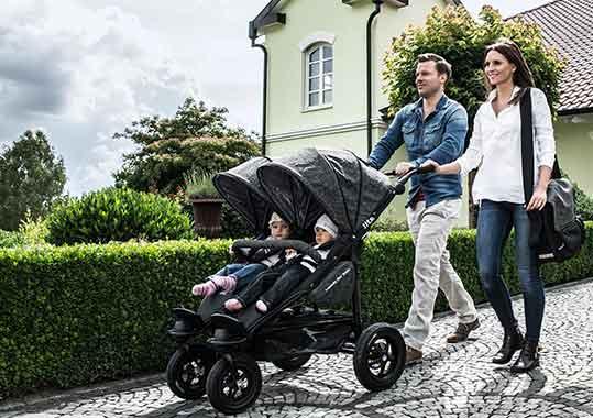 Eltern mit Kindern im Zwillingswagen