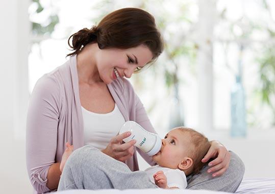 Mutter füttert mit Babyfläschchen