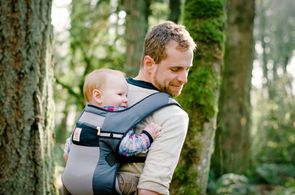 Mann trägt Babytrage auf dem Rücken