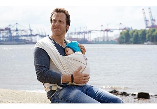 Mann mit Baby im Tragetuch