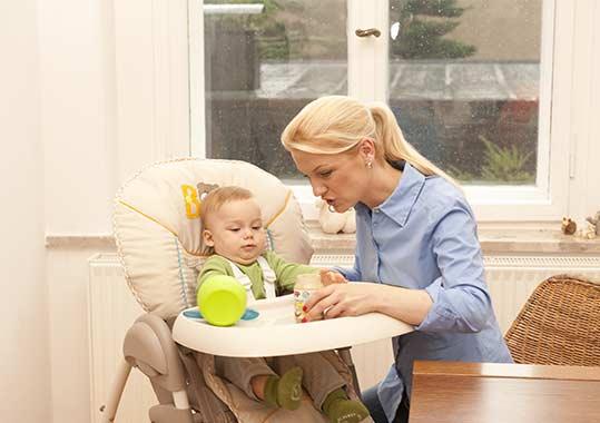 Mama füttert ihr Kind im Hochstuhl-Aufsatz.