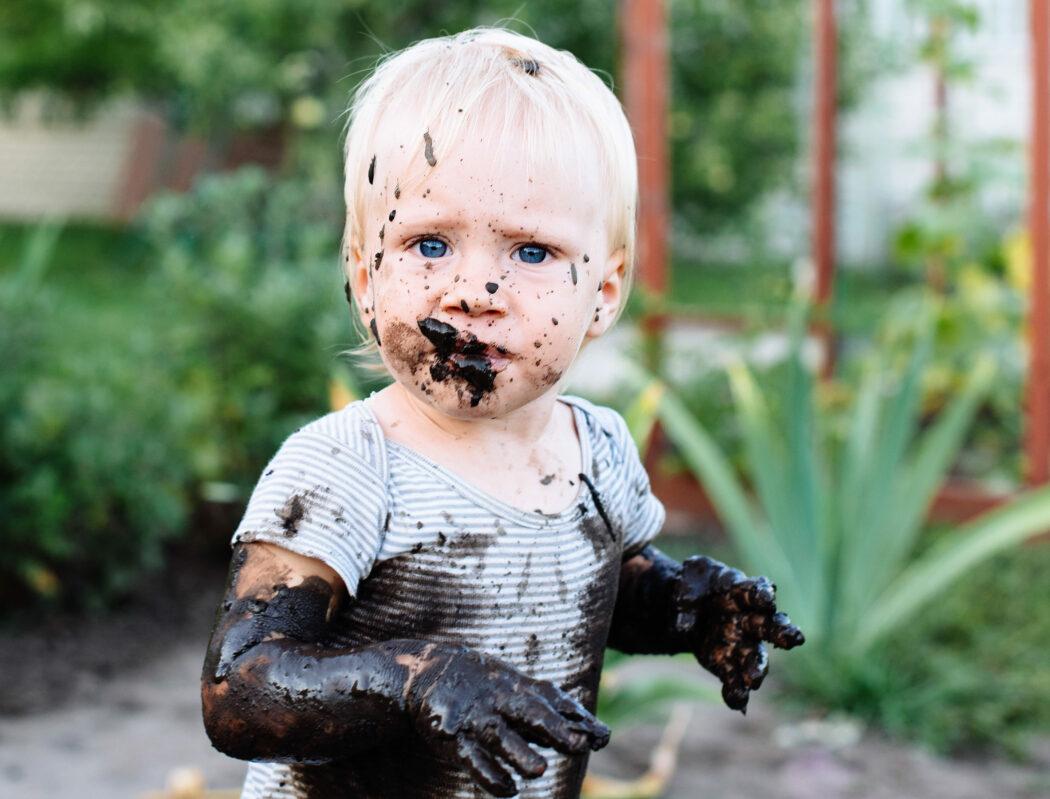 schmutziges kind spielt im matsch