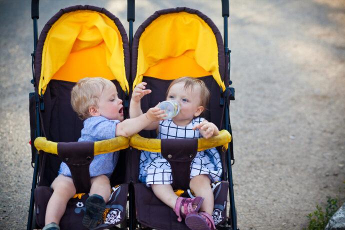 geschwisterwagen nebeneinander zwillinge sitzen zusammen im kinderwagen