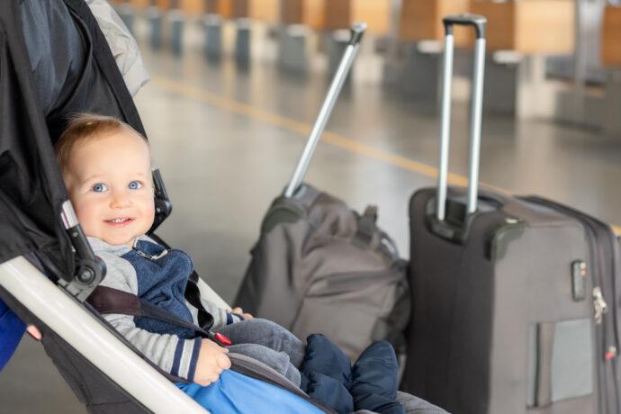 reisen mit baby, baby sitzt im buggy, reisen mit kleinkind, baby koffer flughafen