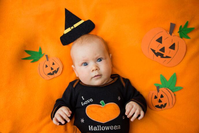 halloween kostuem baby schwarzer body auf orangem hintergrund