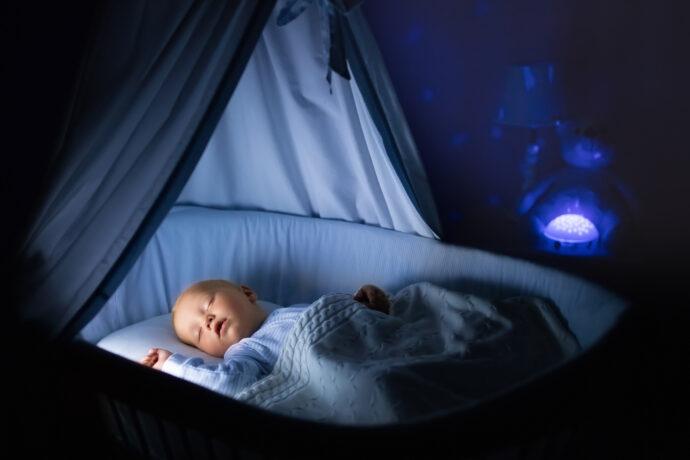 baby liegt mit eingeschaltetem nachtlicht schlafend im bett